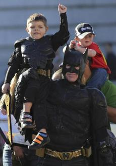 Batkid waved to the crowd from Batman's shoulders.