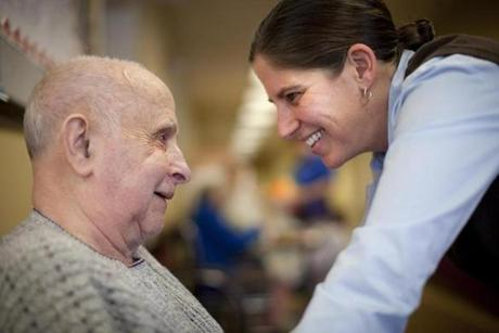 Erica Labb, program director of the dementia care unit at Life Care Center of Nashoba Valley, engaged with resident Richard Pinkham.