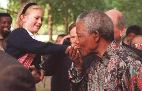 Mandela kissed the hand of an unidentified girl during a stroll in a London park.