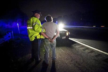 "State Police Trooper Matthew Sheehan takes a suspected drunk driver into custody along Interstate 93. A breath test later indicates the driver's blood alcohol content is 0.17. Sheehan is on ""saturation patrol"" looking for drunk drivers."