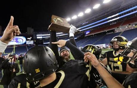 Bishop Fenwick assistant coach Dave Dugan hoisted the trophy after a 28-0 win Saturday night.