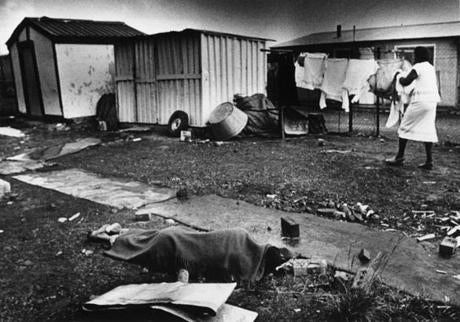 January 26, 1986:  Mourners at the funeral of murdered black community leader, Chief Ampie Mayisa, hacked to death a man they accused of taking part in the killing. The body of 20 year old Petrus Mahamutse lay under a blanket while a woman took in her wash.