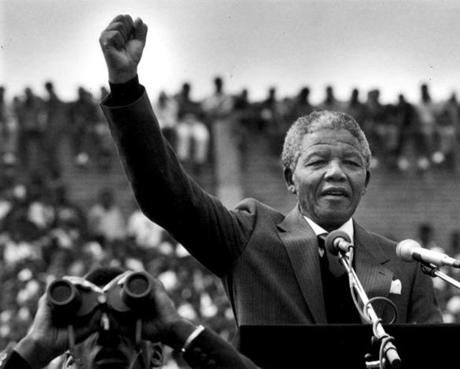 February 13, 1990:  Nelson Mandela gestured to supporters in Soweto two days after his release from prison in Cape Town. He addressed more tha 100,000 people inside a soccer stadium saying,