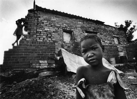 March 11, 1990:  Children at Weiler's Farm, a squatter settlement in a converted pigsty south of Soweto. The previous owner of the farm stopped raising pigs and cattle when he found he could make more money renting out stables and pigsties to people. There were more than 7 million homeless people in South Africa.