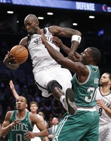Kevin Garnett grabs the ball from Brandon Bass.