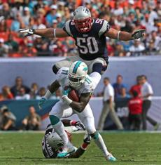 Rob Ninkovich took to the air to try to bring down Wallace.