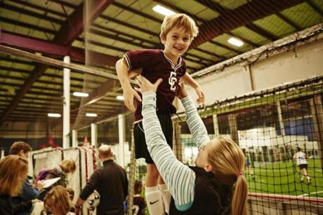 Forward Kendall Coyne gets playful with Callen Beveridge, a member of her host family, before his youth soccer game.