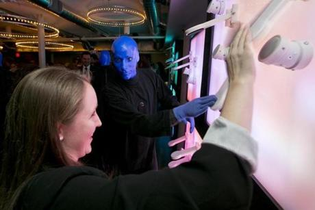 BU student Megan Tucker meets a Blue Man in the Charles's refurbished lobby.