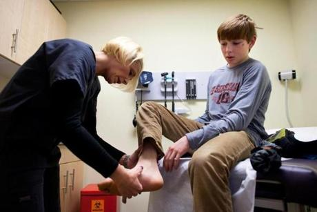 Luke Jones has his foot examined by nurse Jeanette Bajgot at CareWell Urgent Care in Needham.