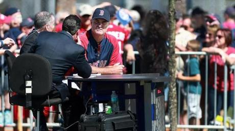 John Farrell waited to do an interview with ESPN on a table put near one of the practice fields.