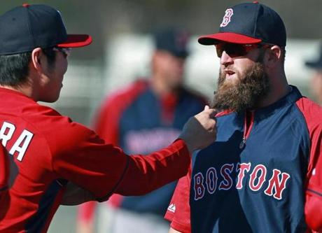 Mike Napoli has kept his long beard, and Koji Uehara could not resist giving it a pull.