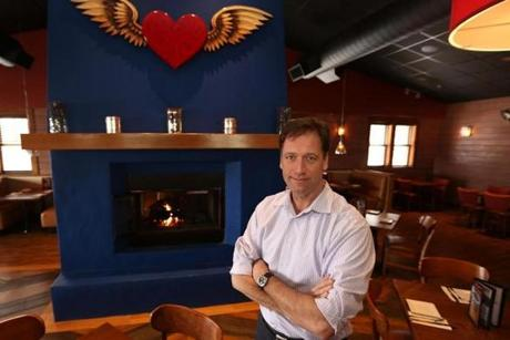 Restaurant owner Jon S. Tosi Jr. stands by the welcoming fireplace and red-heart logo, which hovers like a guardian angel of good Mexican cuisine.