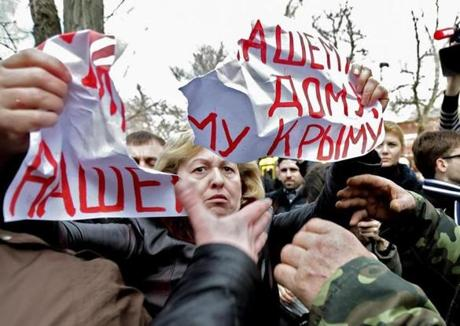 "A group of men ripped apart a sign reading ""Peace for our home, our Crimea!"" held by a woman protesting Russian troops in Simferopol, Ukraine, on Wednesday."