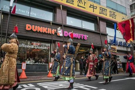 A stream of men dressed as traditional Korean guards marched past a Dunkin' Donuts store in Seoul.
