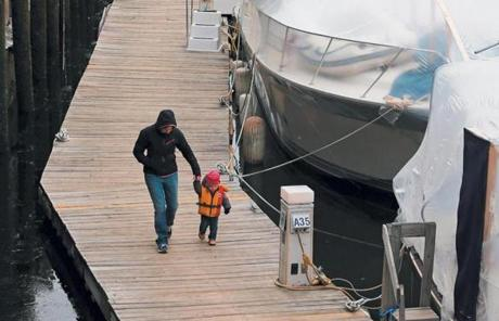Garant and her 20-month-old daughter, Maya, stroll on a dock at Constitution Marina in Charlestown, where several boats have been adapted for winter living.