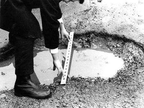 March 9, 1967: A Boston DPW inspector used a ruler to get the dimensions of this pothole.