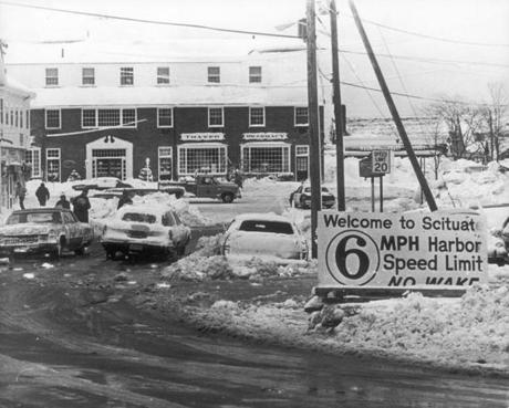 February 8 1978 / fromthearchive / Globe Staff photo by Dan Sheehan / A sign meant for boaters approaching the the entrance to Scituate harbor landed in downtown Scituate during the blizzard of 1978. The 'no wake' rule could apply to the car sunk in the water just beyond the sign.