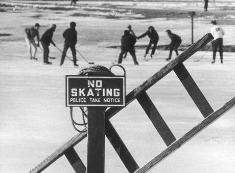 February 10, 1971:  The posted sign on the Fens, accompanied by some primitive rescue equipment, was no deterrent to the skaters in the pond's spirited hockey game.