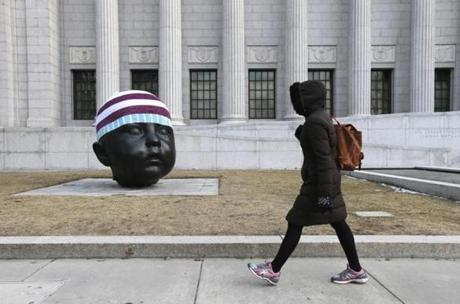 Boston, MA - 03/25/14 - Passerby's walk past a knit hat adorned bronze sculpture by Antonio Lopez Garcia outside the Museum of Fine Art. Attached was a label
