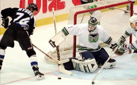Hartford Whalers' goalie Sean Burke clears a shot by Tampa Bay Lightning's Brantt Myhres in the first period of the last game ever for the Hartford Whalers. The team is leaving Hartford for an unknown destination. Hartford's Kevin Haller comes in at right . (AP Photo/Bob Child)