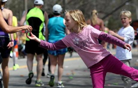 04-21-14, Newton, MA: Cece Robinson stretches as she hands water to a runner on Heartbreak Hill in Newton, Mass. during the Boston Marathon, Mass. April 121, 2104. She is eight years old. Photo/John Blanding, Boston Globe staff story/, SPT( marathon )