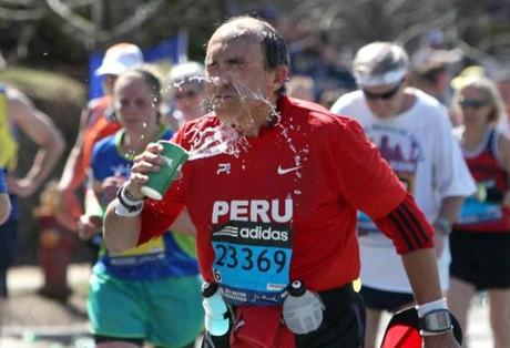 04-21-14, Newton, MA: Manuel Del Rio of Peru (no. 23369) cools off at a water station as he climbs Heartbreak Hill in Newton, Mass. during the Boston Marathon, Mass. April 121, 2104. He is from Swampscott. Photo/John Blanding, Boston Globe staff story/, SPT( marathon )