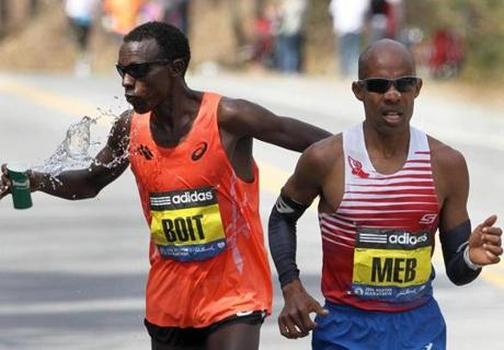 Wellesley, MA--4/21/2014--Josphat Boit (cq), USA, shadowed Men's winner Mebrahtom Keflezighi (cq) #19, USA, for a good part of the race. Boit takes water past Mile 12 in Wellesley. The 118th Boston Marathon is run, on Monday, April 21, 2014. Photos by Pat Greenhouse/Globe Staff Topic: 22marathon Reporter: XXX