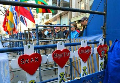Spectators stood at the site of the first bomb on Boylston Street as a small memorial sign for the victims of the 2013 bombings was tucked away next to the sidewalk.