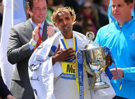 Boston04/21/14- At the Boston Marathon at the finish line ground level on Boylston Street mens winner Meb Keflezighi holds his trophy during the national anthem at the victory ceremony. Boston Globe staff photo by John Tlumacki(metro)