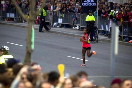 4/21/2014 - Boston, MA - Boylston Street - Buzunesh Deba, cq, of Ethiopia, looked over her shoulder on the home stretch of Boylston Street as she came in for a second-place finish. Officials expected a million spectators to turn out for the 2014 Boston Marathon, on year after the Boston Marathon bombings that killed 3 and injured hundreds. Topic: 21marathonpix. Dina Rudick/Globe Staff.