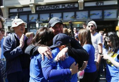 Boston, Massachusetts -- 04/21/2014-- Paul Strong, of Wakefield (C) embraces his wife Shannon and son Colin, 12, during a moment of silence at 2:49 in front of Marathon Sports at the Finish Line of the Boston Marathon in Boston, Massachusetts April 21, 2014. Jessica Rinaldi/Globe Staff