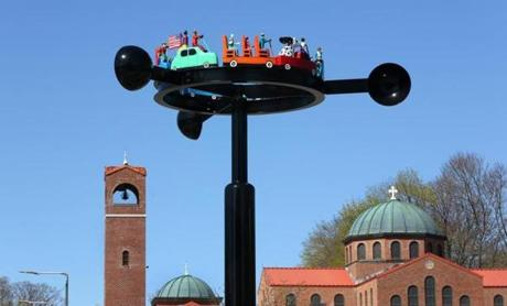 "The public art sculpture ""Traffic"" by George Greenamyer is viewed against the backdrop of Saint Nectarios Greek Orthodox Church in the square."