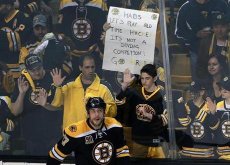 Milan Lucic captured during warm-ups, in front of a sign imploring Montreal not to do any