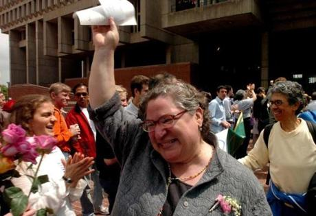 GAY MARRIAGE REMOTE TRANSMISSION -- REMOTE TRANSMISSION--- Boston, Ma-- May 17, 2004 Angela Giudice (Cq) holds walks out of Boston City Hall while holding up hig her marriage license to her partner Nia-Sue Mitchum (cq and walking behind her) both of Roxbury as they walk out into a cheering crowd at Boston City Hall on Monday. photo by Essdras M Suarez/Globe staff outtake