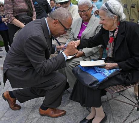 BOSTON, MA - 5/20/2014: Governor Deval Patrick with honor kneels down in front of Adelaide Cromwell, President , The Heritage Guild, co-founder of African Studies to shake her hand. Smiing in the background center is Dr Vivian Johnson, Researcher The Heritage Guild. . New Historic marker honors Zipporah Potter Atkins who purchased her home in 1670 at the site on the Rose Kennedy Greenway by Hanover Street in the North End section of Boston. Governor Deval Patrick and members of The Heritage Guild unveiled and dedicated the plaque etched in granite. (David L Ryan/Globe Staff Photo) SECTION: METRO TOPIC stand alone photo