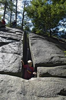 "A child explores the rock crevice known as ""Fat Man's Misery"" at Purgatory Chasm in Sutton."