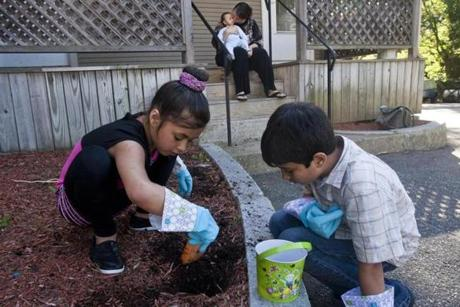 Boston, Mass. -- 6/16/14 The Chaudhry family spends time together outside Monday evening, June 16, 2014. Nadia, 9, and Joel, 8, dig for worms in the front yard of their shelter house, while Michelle Chaudhry kisses her 4-month-old baby, Khalid, on the porch. Homeless and unable to survive on their own, the family now lives in a shelter home in Hyde Park. Zack Wittman
