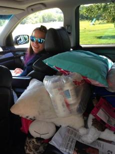 Justina gathered her things in her mother's car in preparation to go home.