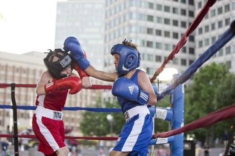 Richie Hogan (left) fought Padraic Folan in the 72.6-pound division during the first Mayor Martin J. Walsh Neighborhood Youth Challenge Connemara vs. Boston Boxing Tournament on City Hall Plaza.