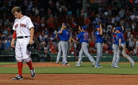As the Chicago Cubs celebrated their victory over the Red Sox, Brock Holt walked off the field after being stranded on base when teammate Dustin Pedroia was called out at first base at Fenway Park.