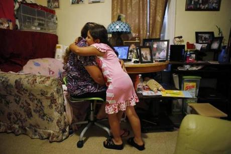 Petrona Interiano of East Boston is embraced by her daughter Nataly, 5,  after she began crying while talking about her brother Santos.
