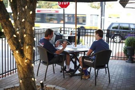 Scott Martin and his son Prescott Martin of Fairfax, Va., enjoy dinner on the patio at Menotomy Grill.