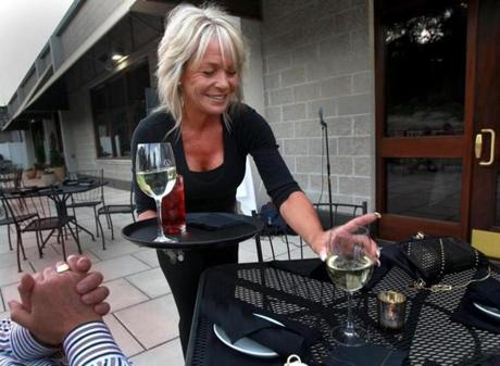 Janice Santarpio serves pre-dinner wine on the deck outside Rosaria Steakhouse.