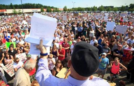 Steve Paulenka, who was just fired from Market Basket, held up a stack of petitions he said were signed by customers in support of bringing back the former CEO Arthur T. Demoulas.