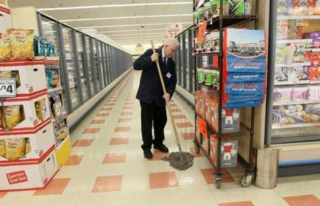 Market Basket worker Antonia Rosa mopped a relatively empty aisle in Lowell.