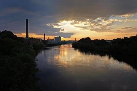 The sun sets over the city of Lowell on the Merrimack River.
