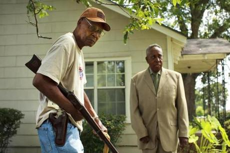 John Watters (left) and Robert Miles Jr., stood outside the Batesville. Miss., home of the late Robert Miles Sr., a farmer and local civil rights movement leader. The older Miles welcomed Freedom Summer volunteers in 1964, introducing them to the black community, finding them housing, and helping them get the lay of the land. At night, the volunteers -- trained in nonviolence -- watched men such as Miles, his son, and Watters slip into the shadows with guns to stand watch in self-defense against violent vigilantes from the Ku Klux Klan.