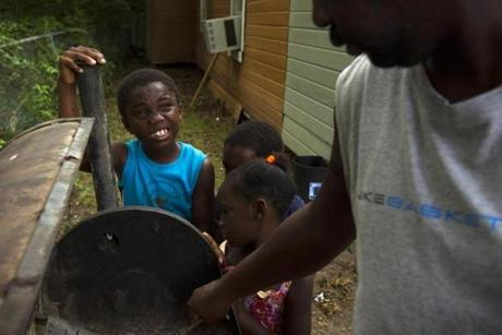 8/9/14 - Greenwood, MS - Sintrelliz Clay, cq, 7, watches as Anthony Lucas, cq, right, cleans out the smoker before a birthday party on Saturday afternoon, August 9, 2014. Topic: 31freedom. Story by Eric Moskowitz/Globe Staff. Dina Rudick/Globe Staff