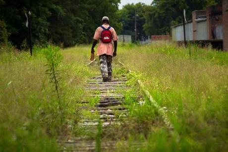 8/9/14 - Greenwood, MS - A man walks disused tracks in Greenwood, MS, bottle in hand. Topic: 31freedom. Story by Eric Moskowitz/Globe Staff. Dina Rudick/Globe Staff