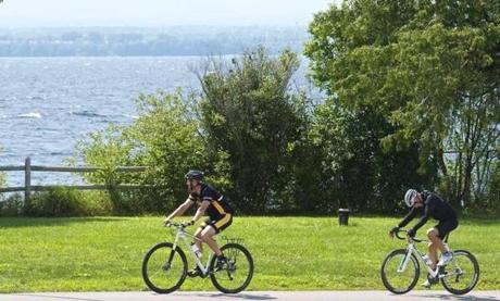 Two cyclists head up the road in Grand Isle, one glancing at Lake Champlain and New York State across the way. Photo by Dirk Van Susteren.